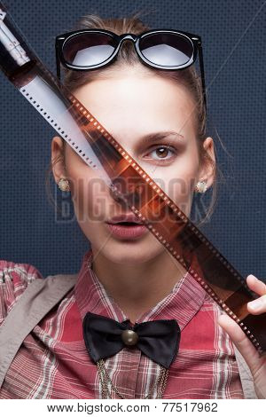 Smiling Hipster Girl Watching Footage On Film. Trendy Teenager In  Checkered Red Shirt And Bow-tie