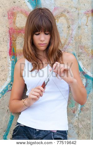 Pretty depressed teenage girl preparing to cut her wrists open