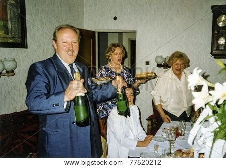 Vintage photo of family celebrating elderly couple's wedding anniversary, eighties