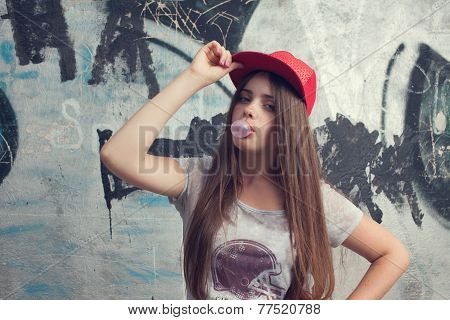 Trendy Beautiful Long Haired Yuong Model Posing On Graffiti Background. Blowing Bubblegum. Red Cap.