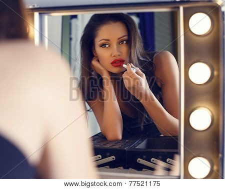 Sexy Woman With Dark Hair Doing Makeup,looking At The Mirror