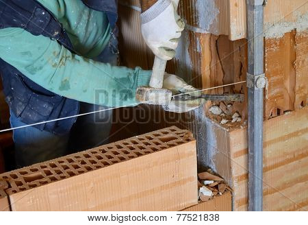 Worker with chisel on an internal wall