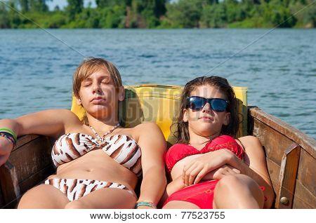 Cute teenage girls sunbathing on the boat on sunny summer day