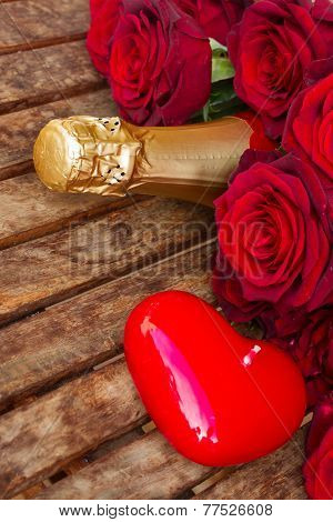 crimson  red  roses with neck of champagne