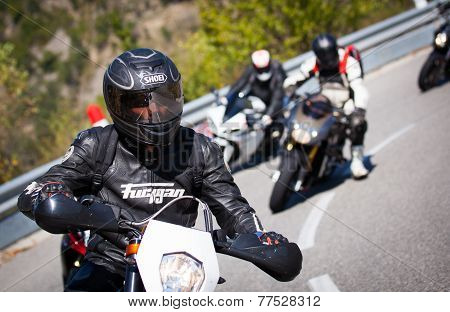 motorcyclist racers passing on road in french alps