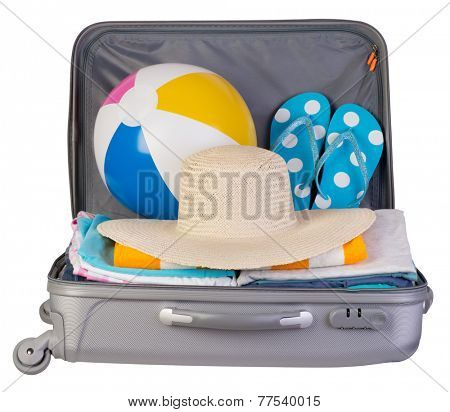 Packed  suitcase full of vacation items isolated on white background