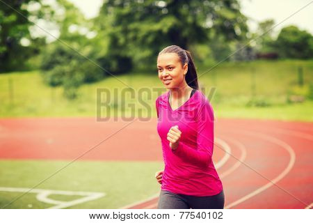 fitness, sport, training and lifestyle concept - smiling african american woman running on track outdoors