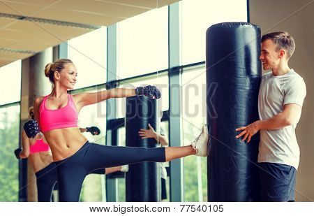 sport, fitness, lifestyle and people concept - smiling woman with personal trainer boxing in gym