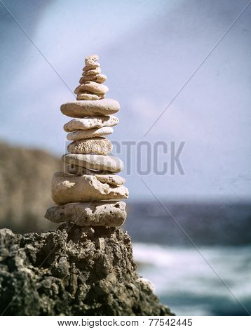 Concept of Balance - Stacked pebbles and fossil corrals at rocky coast. Vintage processing.