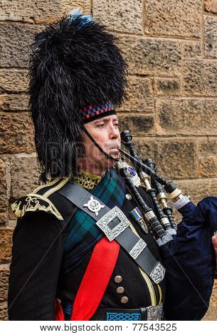 Portrait Of A Military Dressed Bagpiper Playing The Bagpipe
