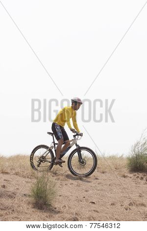 young man wearing rider suit riding mountain bike MBT on dusty road use for sport activities and mal