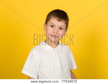 grimacing boy portrait on yellow background