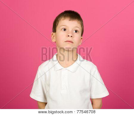 grimacing boy portrait on pink background