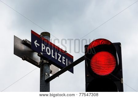 a traffic light shows red light. with the sign police