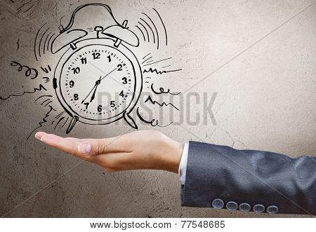 Close up of businesswoman holding alarm clock in palm