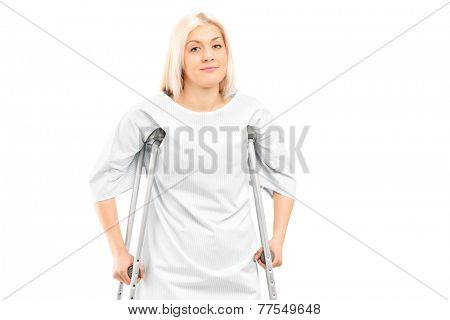 Female patient posing with crutches isolated on white background