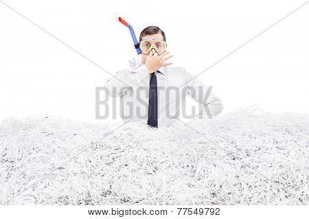 Businessman diving into a pile of shredded paper isolated on white background