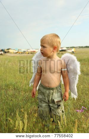 little boy with angel wings on the airfield