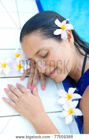 Young hispanic woman with long black  hair, eyes closed relaxing by the swimming pool