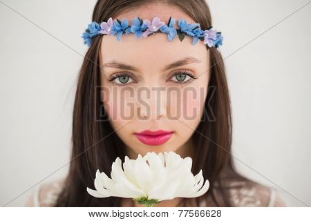 Pretty hippie smelling a flower against a grey wall