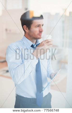 Businessman holding disposable cup and tablet looking out the window in his office