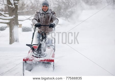 Man using snowblower to clear deep snow on residential driveway after heavy snowfall