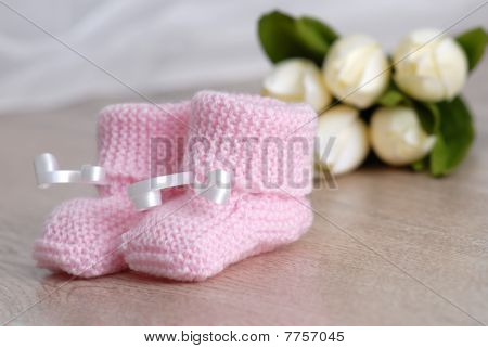 pink baby booties with flowers in the background