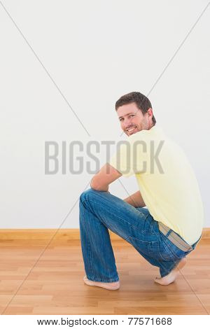 Casual man crouching on floor looking at wall at home in the living room