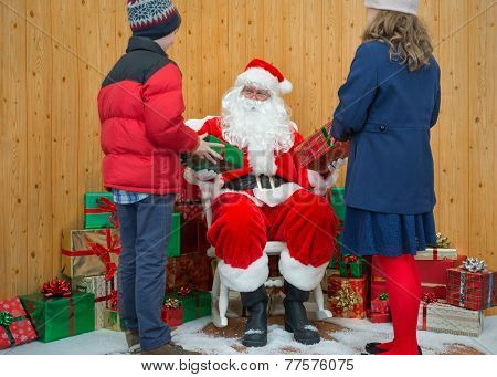 A boy and a girl receiving Christmas gifts from Santa in his grotto