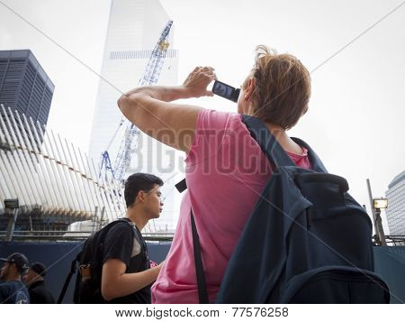 NEW YORK - SEPT 11, 2014: A tourist takes a picture of the Freedom Tower and structures at the WTC site on the anniversary of the 2001 September 11 terrorist attacks in Lower Manhattan.