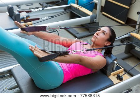 Pilates reformer workout exercises woman brunette at gym indoor