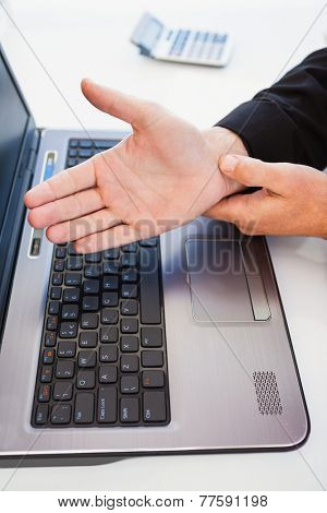 Hand of man touching his wrist in the office