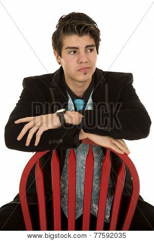 Man In Blac Suit Sit Backwards On Red Char Look Side