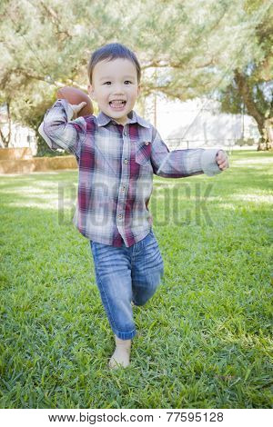 Cute Young Mixed Race Boy Playing Football Outside At The Park.