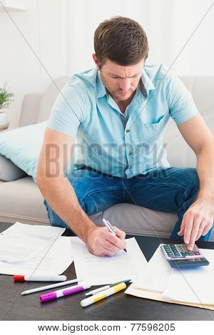 Concentrate man at home counting his bills in a sofa
