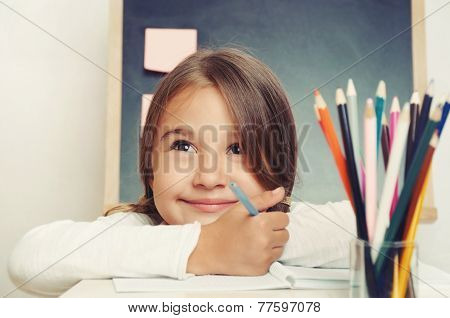 Portrait Of Cute Lovely Girl Drawing In Copybook On Blackboard Background