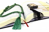 pic of quran  - whipped Quran with green rosary before light background