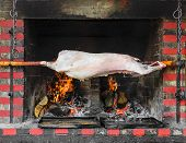picture of spit-roast  - Pig on a spit over a fire - JPG