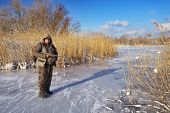 stock photo of hunter  - Hunter on the ice pond waiting victim - JPG