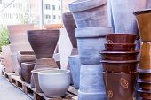 pic of wooden pallet  - Glazed and unglazed ceramic flower pots in a variety of sizes and colors stacked on wooden pallets outside a pottery warehouse or commercial store - JPG