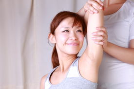 foto of chiropractic  - portrait of young Japanese woman getting chiropractic - JPG