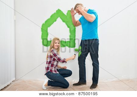 Woman Painting Jeans Of Young Man