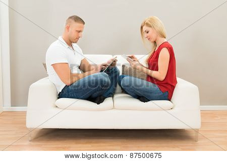 Couple On Sofa Using Digital Tablet