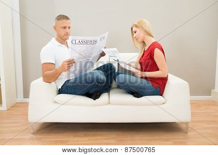Couple On Sofa With Newspapers