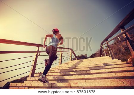 young woman runner running up on stone stairs sunrise seaside