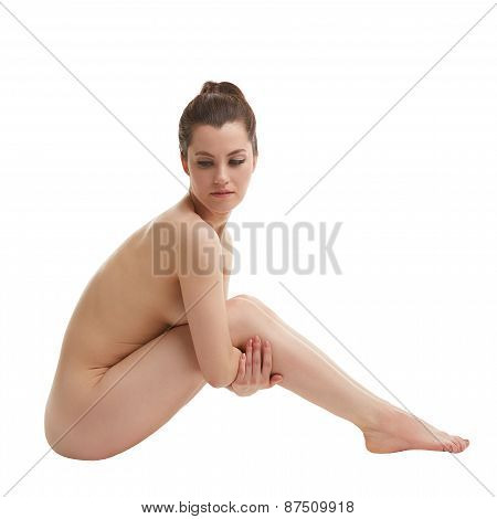 Attractive nude woman posing hugged her legs