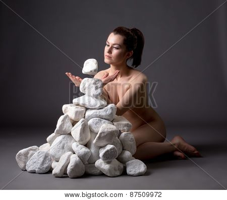 Telekinesis. Naked woman moving stones mentally