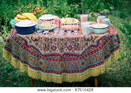 Decorated Table Covered With An Old Tablecloth.