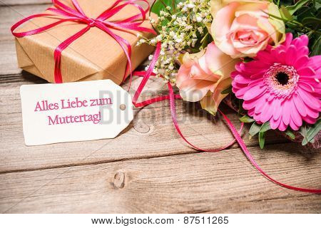 Bunch of flowers and tag with german text on wooden background. Happy Mother's Day