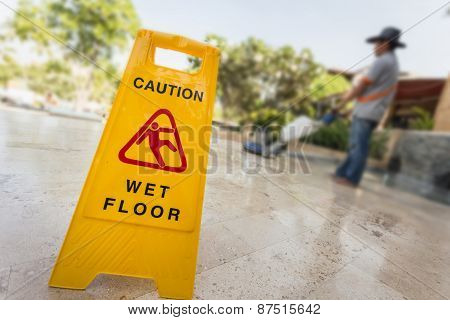 Yellow Caution Sign And Blur Of Man Doing Floor Polishing